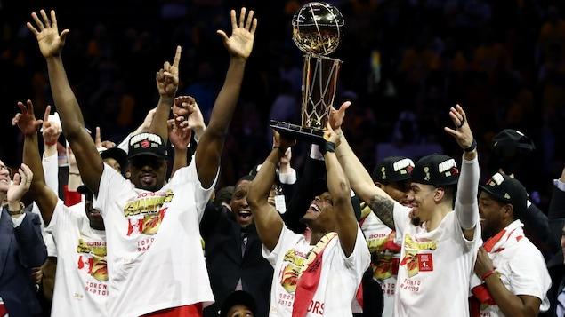 Des joueurs lèvent les bras en triomphe avec un trophée