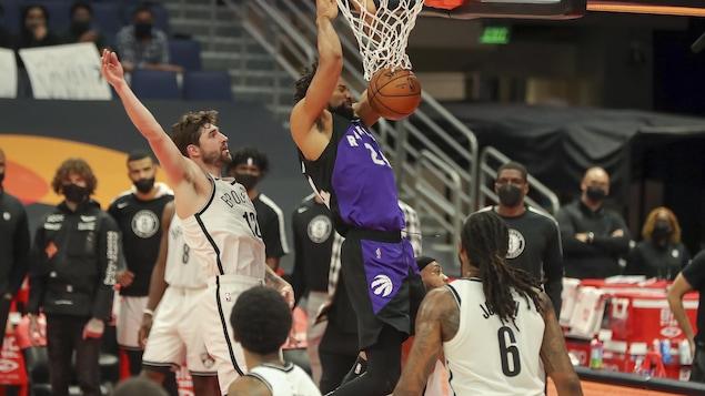 Le joueur de centre des Raptors s'accroche au panier après avoir passé le ballon dans le filet, au-dessus de joueurs des Nets impuissants.