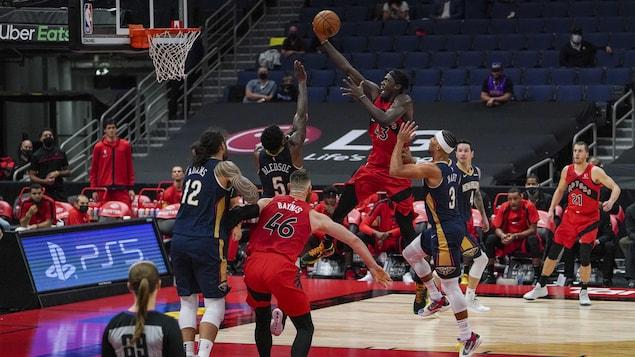 Un joueur de basketball tente d'inscrire un panier malgré la présence d'adversaires autour de lui.