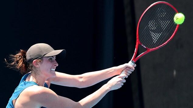 Une joueuse de tennis vêtue de bleu et portant une casquette noire frappe la balle du revers.