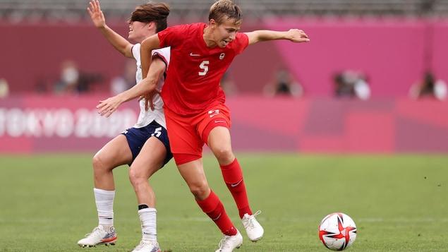 Dos atletas entran en contacto mientras compiten por el balón durante un partido de fútbol femenino.