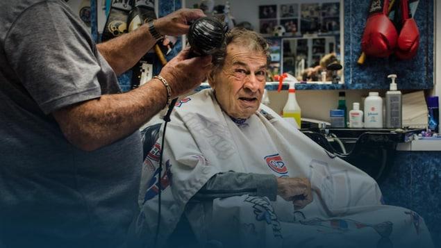 Assis sur une chaise de coiffeur, Régis Lévesque se fait sécher les cheveux.