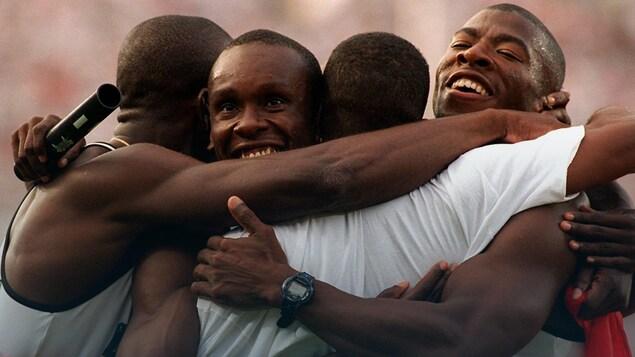 Quatre hommes s'enlacent.