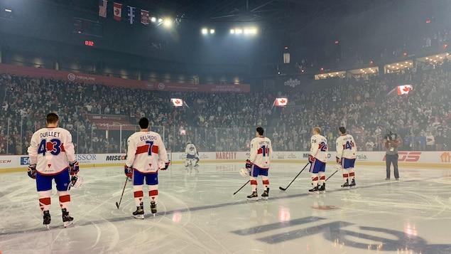 Des joueurs du Rocket se tiennent debout au centre de la patinoire devant une foule pleine.