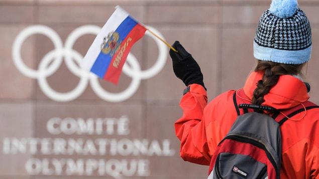 Elle agite un drapeau de la Russie.