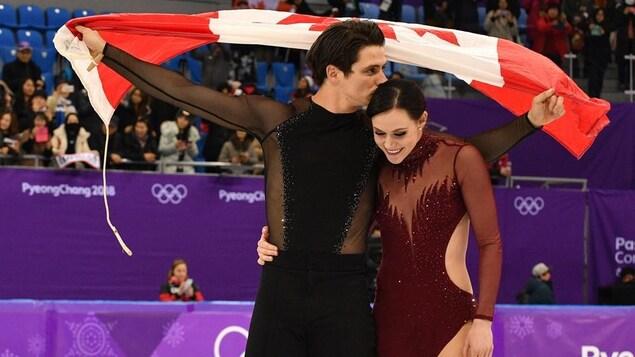 Scott Moir donne un baiser sur la tête de Tessa Virtue avec le drapeau du Canada