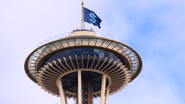 La drapeau du Kraken de Seattle flotte au mât de la tour Space Needle, emblème architectural de la ville.