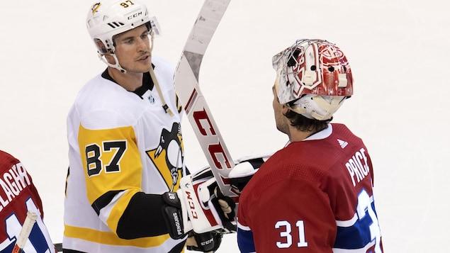 Deux joueurs de hockey échangent quelques mots au centre de la patinoire.