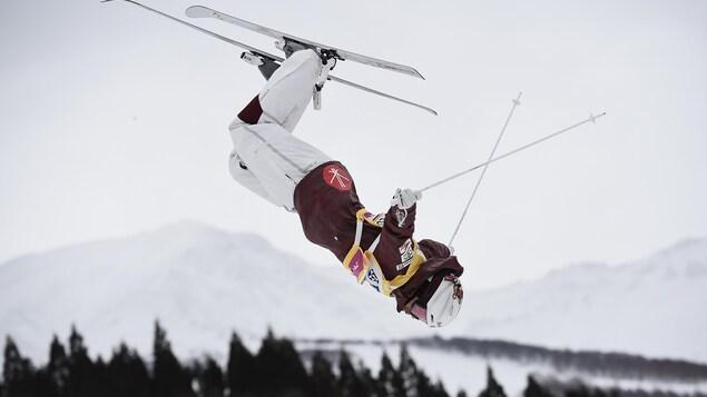 Le Canadien Mikaël Kingsbury en plein saut, durant une descente