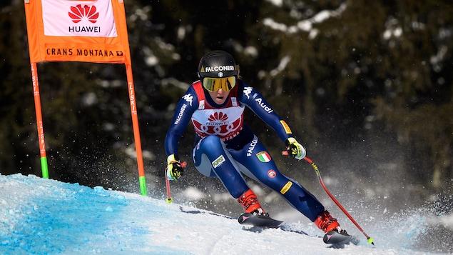 La skieuse négocie un virage à haute vitesse.