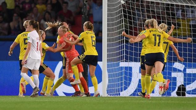 Les Suédoises célèbrent leur victoire, tandis que Jeanine Beckie marche, déçue.