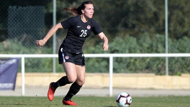 La joueuse de soccer Vanessa Gilles court, ballon au pied, sur un terrain gazonné