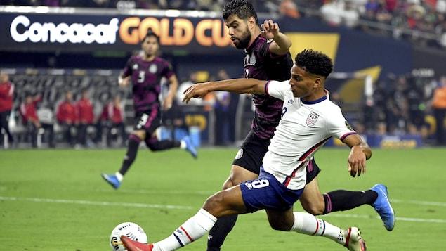 Deux joueurs de soccer tentent de récupérer le ballon.