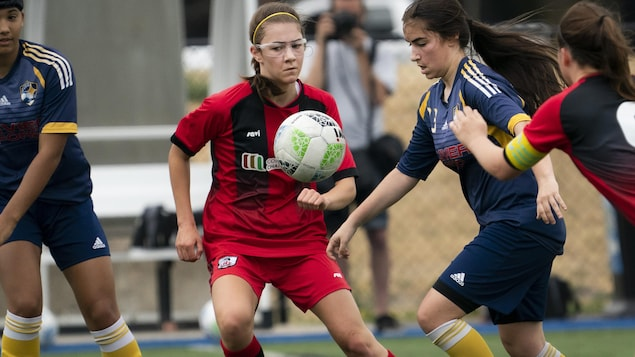 Des joueuses de soccer luttent pour l'obtention du ballon.
