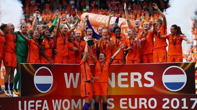 Deux joueuses soulèvent le trophée pendant que leurs coéquipières célèbrent la victoire derrière elles.