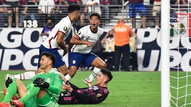 Un joueur de soccer regarde son coéquipier avec enthousiasme après avoir marqué un but. Le gardien adverse et un défenseur sont au sol.