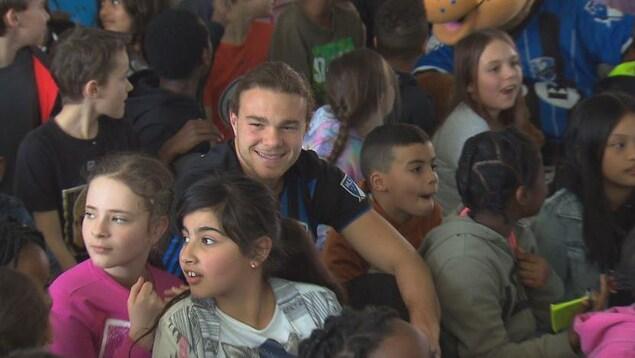 Le milieu de terrain Samuel Piette, de l'Impact de Montréal, sourit au milieu d'un groupe d'enfants à l'école primaire Philippe-Morin, à Lachine.