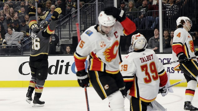 Un joueur de hockey lève les mains en l'air.