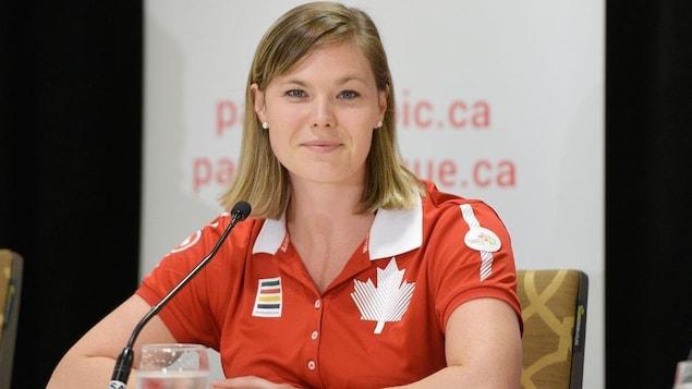Elle porte une chemise au couleur du Canada.