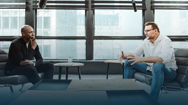 Assis face à face, deux hommes discutent.