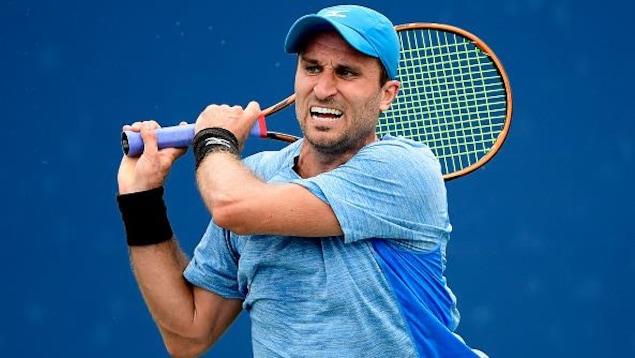 Un joueur de tennis renvoie la balle d'un adversaire.