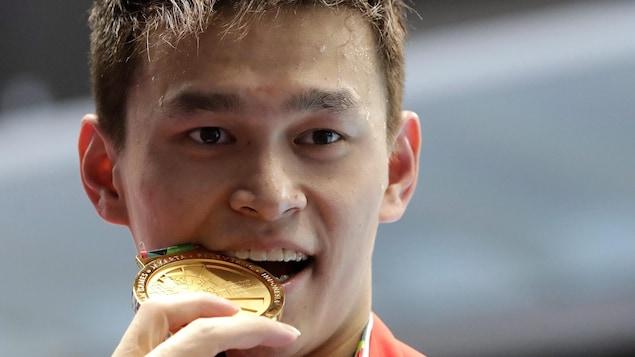 Il croque sa médaille d'or.