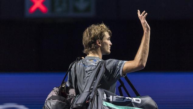 Il salue la foule à son départ du court à Bâle.