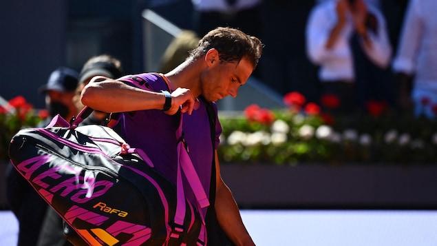 La tête baissée, le joueur de tennis quitte le court avec son sac sur l'épaule droite.