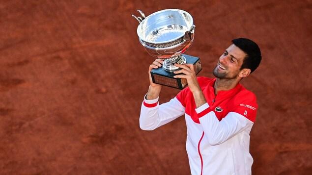 Le trophée dans les mains, il sourit.