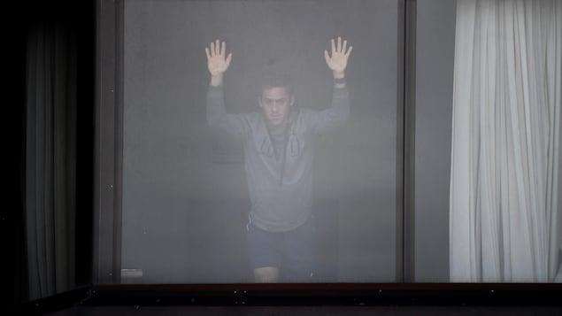 Un homme regarde par la fenêtre de sa chambre d'hôtel.