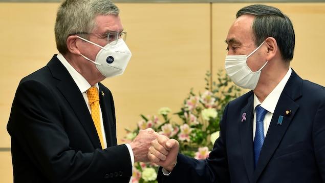 Deux hommes masqués se saluent en se cognant les poings fermés.