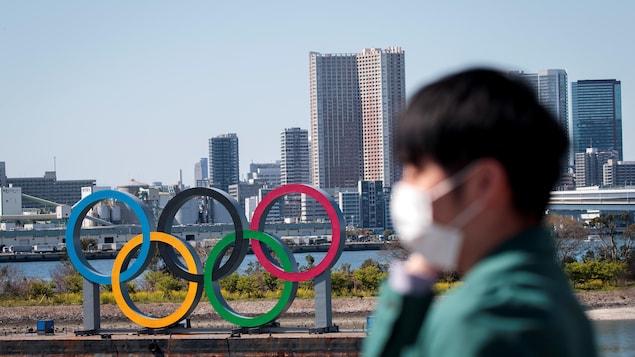 Un homme portant un masque marche devant les anneaux. olympiques à Tokyo.