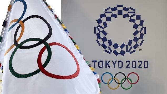 Un drapeau olympique à côté du logo des Jeux de Tokyo
