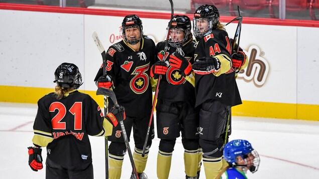 Quatre joueuses de hockey se félicitent après avoir inscrit un but lors d'un match.