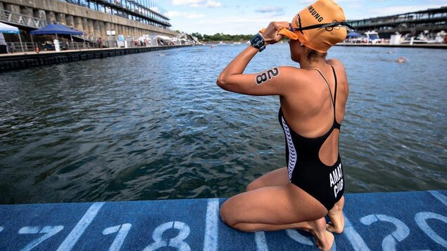 Une nageuse sur un quai ajuste son bonnet et ses lunettes.