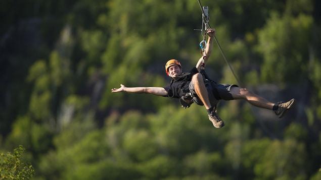 Un homme vêtu de noir avec un casque orange survole la cime des arbres à l'aide d'une tyrolienne dans les Laurentides.