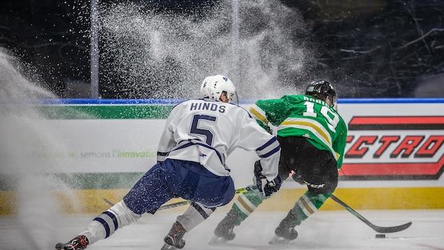 Deux joueurs de hockey freinent pendant un match et soulève un énorme nuage de neige.