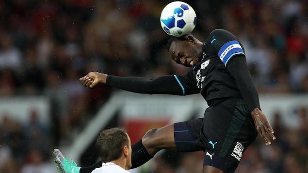 Usain Bolt fait une tête pendant un match de démonstration au profit de l'UNICEF en juin 2018