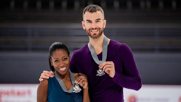 Les deux athlètes tiennent fièrement leur médaille en souriant.