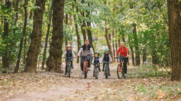 Une famille fait du vélo dans le bois.