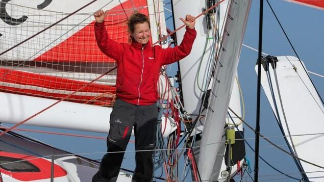 En veste rouge, elle lève les bras sur son bateau.
