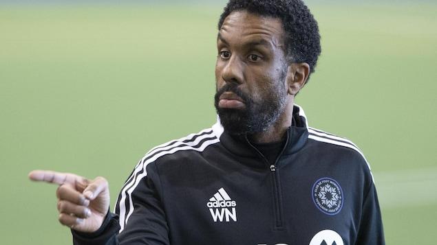 Une entraîneur de soccer pointe du doigt
