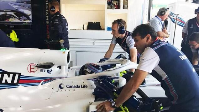 Le personnel de l'équipe Williams recule la voiture de Lance Stroll dans le garage.