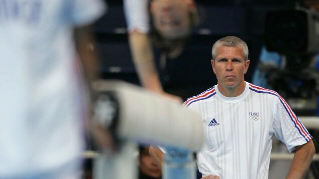 Un entraîneur regarde une athlète s'entraîner à la poutre.