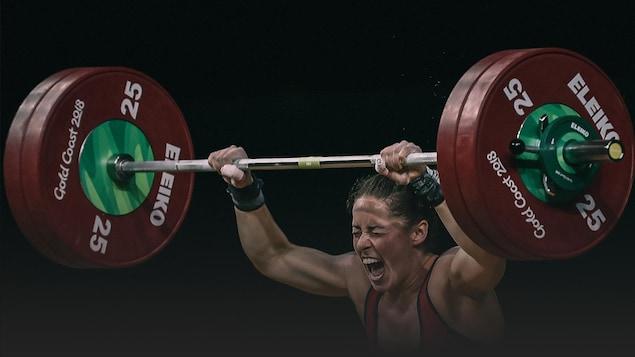 Une haltérophile soulève plus de cent kilogrammes au-dessus de sa tête.