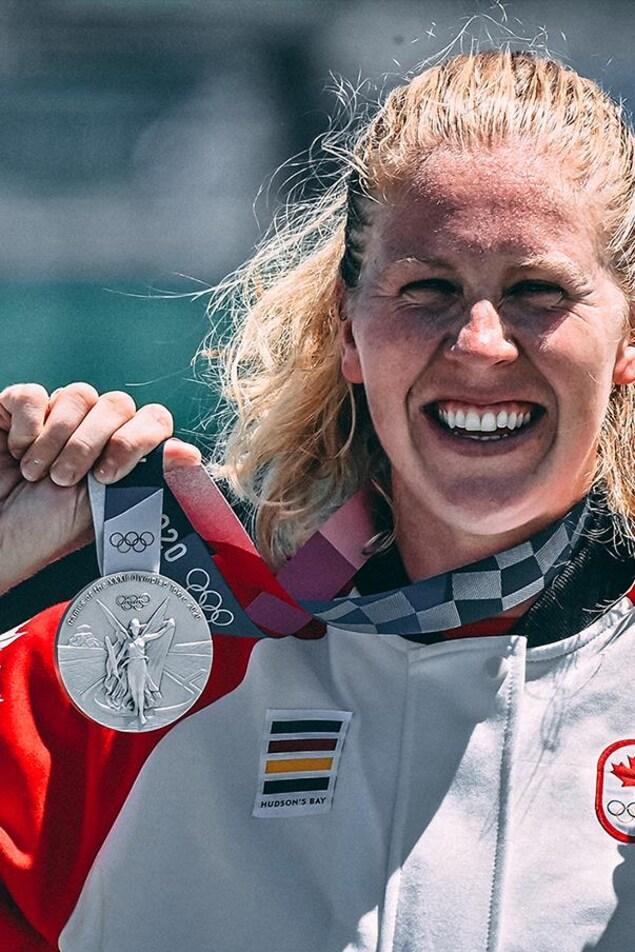 Une femme sourit en brandissant une médaille d'argent.