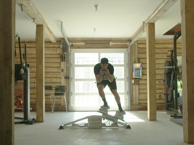 Le skieur alpin Erik Guay s'entraîne à l'intérieur sur un appareil de simulation.