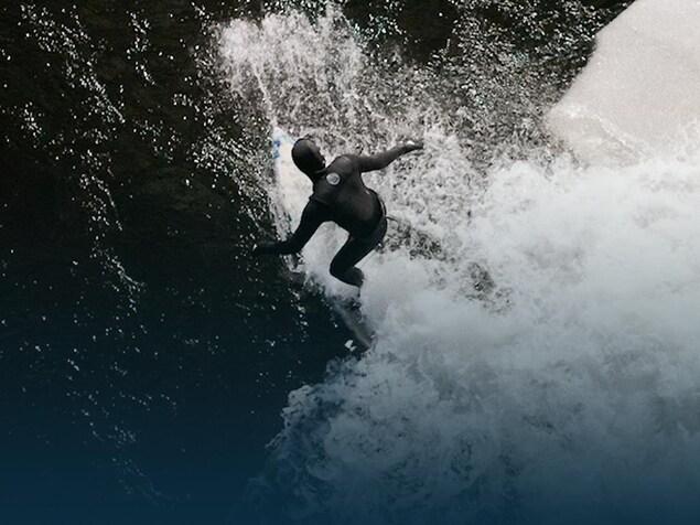 Un surfeur se tient debout sur sa planche près d'un gros morceau de glace.