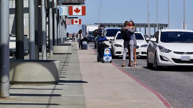 兩名戴著口罩的婦女在一個機場外面擁抱告別。