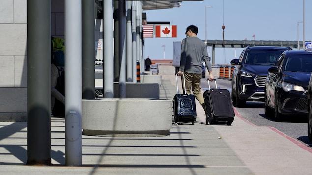 Un voyageur, de dos, transportant deux valises.